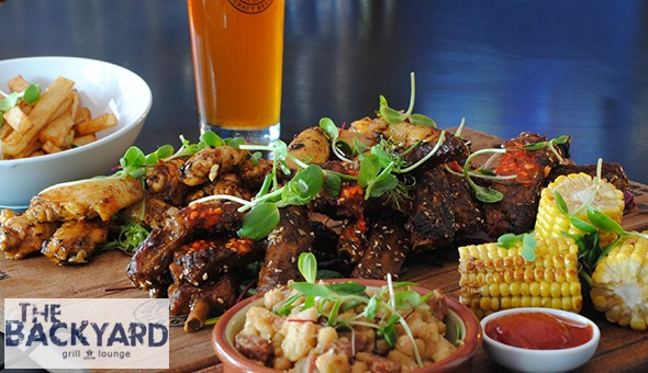 The Monster Meat Board with Sides for 4 People at The Backyard Grill & Lounge, Sea Point! Includes: BBQ Beef Ribs, Rump Steak, Wors, Chicken Wings Skewer, Calamari, Chips, Garlic Roll, Braai Mushroom & Corn on the Cob!